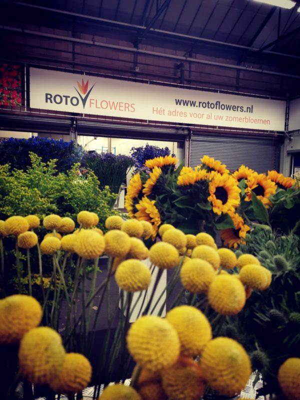 bloemen op tafel met bedrijfsnaam en spanbord op open dag