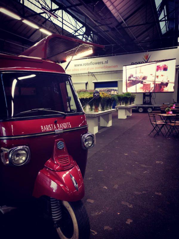 rode piaggio espressotruck met tafels en bloemen op open dag